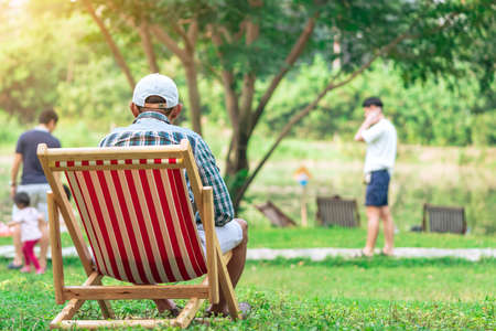 Back view of senior man with white hat sitting on garden chair and by the table in garden. Summer vacation in green surroundings. Happy person outdoors relaxing on deck chair in garden.Outdoor leisure