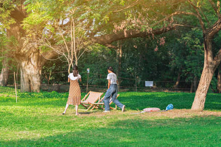 Back view of Asian woman with friends walking together on lawn through green garden.Female relaxing in park. Happiness friends spending time together outside in green nature. Enjoying nature outdoors.