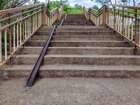 Stair-safe bike ramp along stairs. Comfortable and safe lanes for bicycles on stairs. Old and rusted steel rails for bicycles up and down for comfort between steps on stairs in the public park.