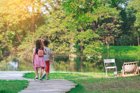 Back view of Asian young girl and boy walking together on pathway through green garden. Sister and brother walking together in park. Happy family spending time together outside in green nature.