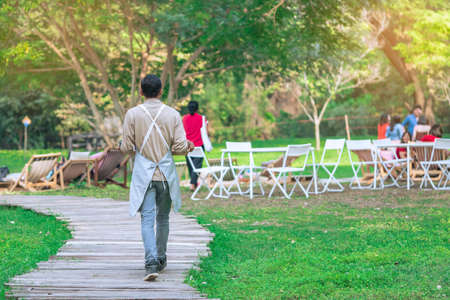Back view of Asian male waiter carry food and beverages along garden paths to serve customers while relaxing in open-air restaurant. People spending time outside in green nature. Enjoying outdoors.