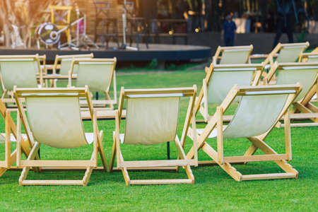 Many empty white deck chairs with tables in lawn is surrounded by shady green grass. Comfortable on outdoor patio chairs in garden.  Lawn chairs in the park. Sunbeds in the garden. Selective focus.