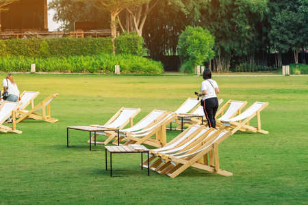 Back view of Asian woman standing among many empty white deck chairs with tables for dinner in lawn is surrounded by shady green grass. Female spending time outside in green nature. Enjoying outdoors. Standard-Bild