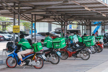 KANCHANABURI, THAILAND-AUGUST 22,2021 : Group of Grab riders park motorbike to relax and wait to get food from the restaurant at parking lot in front of Robinson Department Store. Sajtókép