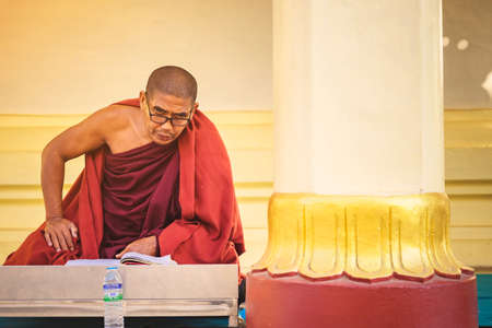 PAGAN-Myanmar, January 21, 2019 : Unidentified monk meditate and pray with Buddhist scriptures at Shwezigon Pagoda on january 21,2019 in Pagan, Myanmar. Sajtókép