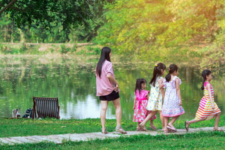 KANCHANABURI, THAILAND-JANUARY 11,2020 : Happiness Asian mother with her daughter and friends walking together on pathway through green garden  at Mulberry Mellow (Open air coffee shop). Sajtókép