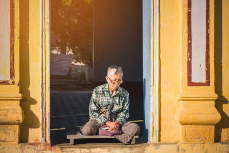 PAGAN-Myanmar, January 21, 2019 : Unidentified people meditate and pray with Buddhist scriptures at Shwezigon Pagoda on january 21,2019 in Pagan, Myanmar.
