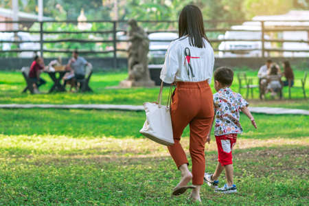 KANCHANABURI, THAILAND-JANUARY 11,2020 : Back view of unidentified Asian mother and her son walking side by side together on lawn through green garden at Mulberry Mellow (Open air coffee shop)