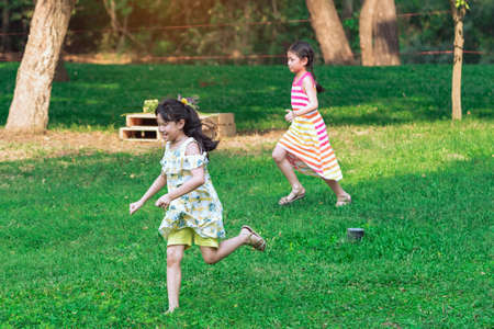 KANCHANABURI, THAILAND-JANUARY 11,2020 : Happiness Asian young girls and friends playing together on lawn through green garden among trees and green grass at Mulberry Mellow (Open air coffee shop).