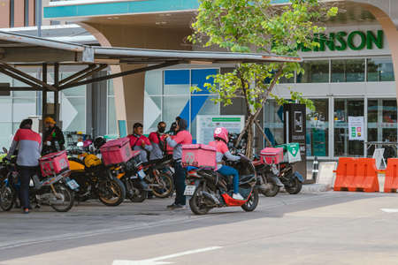 KANCHANABURI, THAILAND-AUGUST 22,2021 : Group of Food delivery service riders park motorbike to relax and wait to get food from the restaurant at parking lot in front of Robinson Department Store. Sajtókép