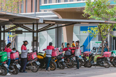 KANCHANABURI, THAILAND-AUGUST 22,2021 : Group of Food Panda delivery service riders wear face mask parking motorbike to relax and wait to get food from restaurant at parking lot in front of Robinson.