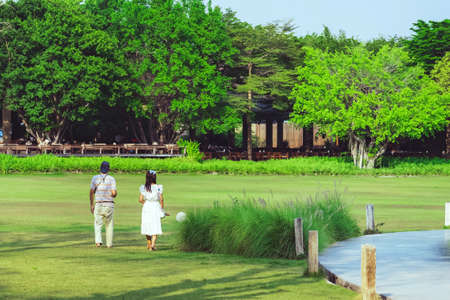 KANCHANABURI,THAILAND-FEBRUARY 20,2021 : Back view of Unidentified Asian cheerful family walking to relax together through green garden at the village farm to cafe restaurant. Enjoying nature outdoors