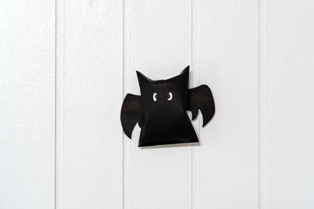 Origami bat made of black paper, isolated on white wooden wall background. Dark paper ghost Halloween party concept origami paper bat. The figure of black paper bat flying over white background. Stock fotó