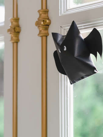 Origami bat made of black paper, isolated on glass window or door background. Dark paper ghost Halloween party concept origami paper bat. The figure of black paper bat flying over white background. Stock fotó