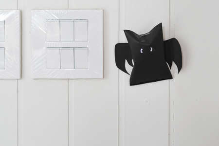 Origami bat made of black paper near light switches on white wall background. Dark paper ghost Halloween party concept origami paper bat. The figure of black paper bat flying over white background.