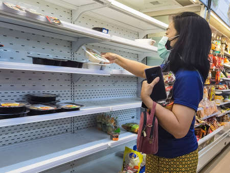KANCHANABURI,THAILAND-AUGUST 11,2021 : Unidentified woman choose food on shelves mostly empty with only a few packages of food left amid panic buying as the coronavirus (COVID-19) spreads at 7-Eleven. Sajtókép