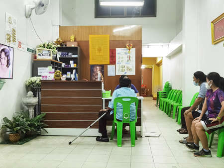 KANCHANABURI,THAILAND - SEPTEMBER 3,2020 : Unidentified orthopedic patients sit in a clinic waiting for their turn to go to the doctor's room at reception of Kijjapat clinic in Kanchanaburi, Thailand. Sajtókép