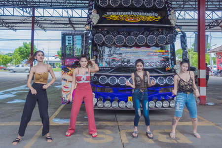 KANCHANABURI THAILAND - SEPTEMBER 1 : Unidentified female tourists dancing in front of a bus at the car park on September 1,2019 in Kanchanaburi, Thailand