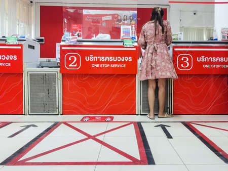 KANCHANABURI ,THAILAND - APRIL 27,2021 : Unidentified Thai people wear face mask with customer floor sign, warning to stay safe and keep social distancing for Coronavirus (Covid-19) at Post office. Sajtókép