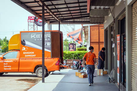 KANCHANABURI,THAILAND-APRIL 6,2020 : Unidentified delivery staff is preparing parcels in to Kerry Express container car to bring to the customers at Kerry Express Company, Kanchanaburi Branch. Sajtókép