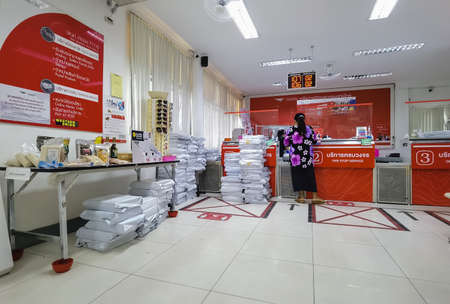 KANCHANABURI ,THAILAND - APRIL 28,2021 : Unidentified Thai people wear face mask with customer floor sign, warning to stay safe and keep social distancing for Coronavirus (Covid-19) at Post office.