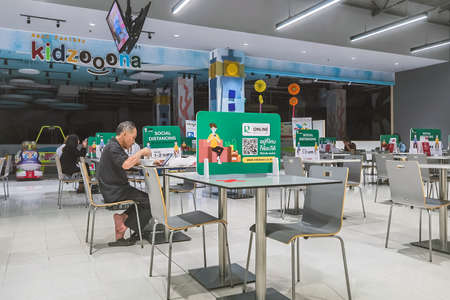 KANCHANABURI,THAILAND-JUNE 11,2021 : Label social distancing sign on table,Space between people to avoid spreading Corona virus (COVID-19).Social distancing at food court in Robinson department store.