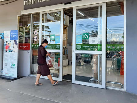 KANCHANABURI,THAILAND-JULY 4,2021 :Unidentified Thai customers wear face masks to prevent germs from corona virus during the Covid-19 pandemic in front of the entrance gate at Tesco Lotus supermarket.