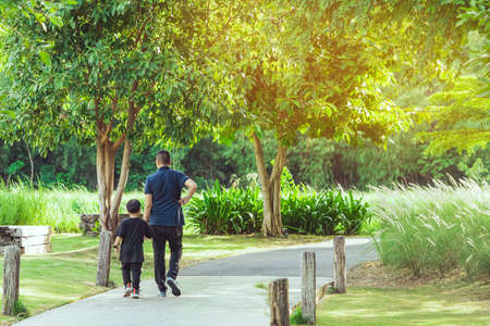 Asian father hand holding lovely son walking on pathway through green garden.Dad and son walking together in park. Happy family spending time together outside in green nature.Enjoying nature outdoors. Stock fotó