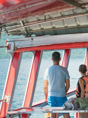 Back view of lover passengers relaxing on balcony enjoying view from boat of Samui island in the sea. Happy casual couple tourists outside on tropical holiday destination. Cruise ship vacation.