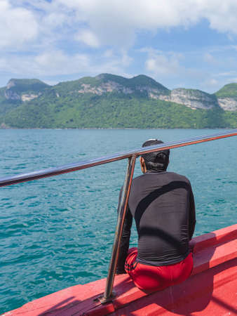 Back view of Asian man in black shirt relaxing on balcony enjoying view from boat of Samui island in the sea. Happy casual male tourists outside on tropical holiday destination.Cruise ship vacation. Stock fotó