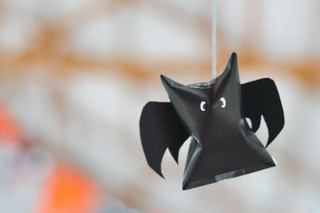 Origami bat made of black paper hanging on a rope for Halloween decorations. Dark paper ghost Halloween party concept origami paper bat. The figure of black paper bat flying over room. Space for text. Stock fotó