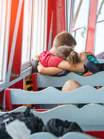 Back view of happiness lover passengers hugging each other while relaxing on balcony enjoying view from boat in sea. Happy casual couple tourists on tropical holiday destination. Cruise ship vacation.