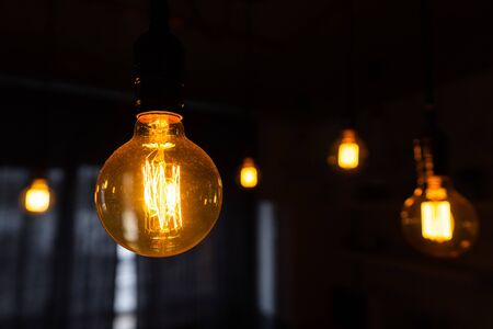 Close-up of incandescent light bulbs hanging in the dark room. Inefficient filament light bulbs waste electricity. Decorative antique edison light bulbs with straight wire. Dimmable, warm white, E27 Archivio Fotografico
