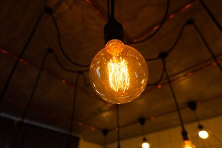 Close-up of big vintage incandescent lights bulb hanging in a dark room. Decorative edison light bulbs with straight wire. Dimmable, warm white, E27. Inefficient filament light bulbs waste electricity