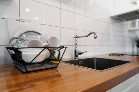 Budget and lightweight antimicrobial dish drainer with drain board at modern scandinavian kitchen. Dish rack holds many dishes and cups against wooden countertop, white wall tiles, sink and faucet