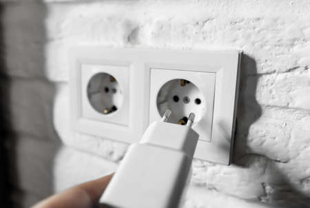 Unplugging idle appliances saves electricity. Idle phone chargers or power adapters. Vampire power, standby power. Plug-in adapter into european wall outlet. USB plug insert into electric wall socket