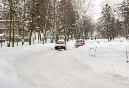 Lutsk, Ukraine - February 12,2020: People on street after snow storm. City street after blizzard. Record-breaking amounts of snow. Uncleaned slippery roads and sidewalk in winter. Cars in snowdrift
