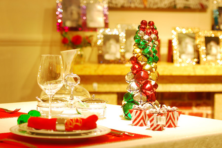 Christmas table setting in traditional red and green with plates, cutlery, wine glasses photo