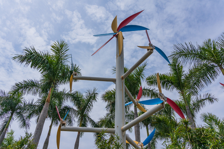 Windmill Surrounded by Palm Tree with Blue Sky Background Stock Photo