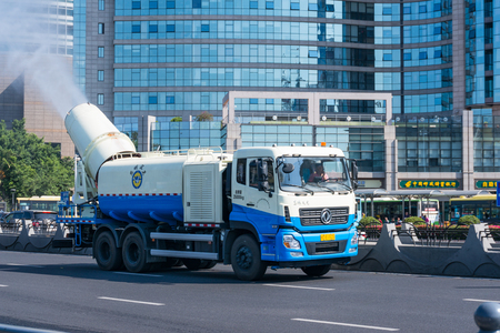 Xiamen, China - May 30, 2018: Fog Artillery Sanitation Truck Work on Road with Modern Building Background