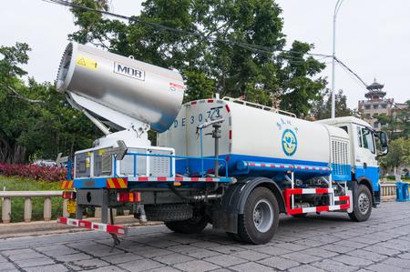Xiamen, China - DEC 31, 2017: Fog Artillery Sanitation Truck Work on Road near Dragon Boat Pool