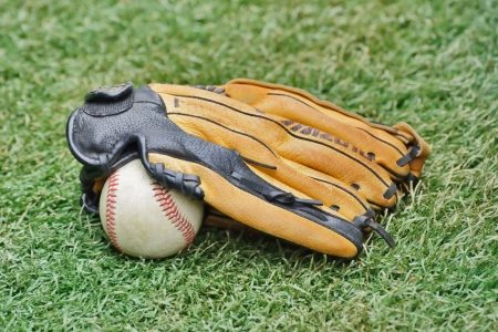 Baseball ball and Glove on grass photo
