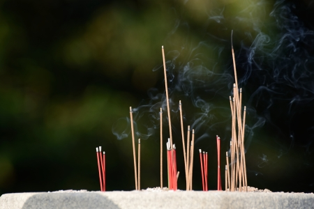 burning joss sticks in Buddhist temple photo