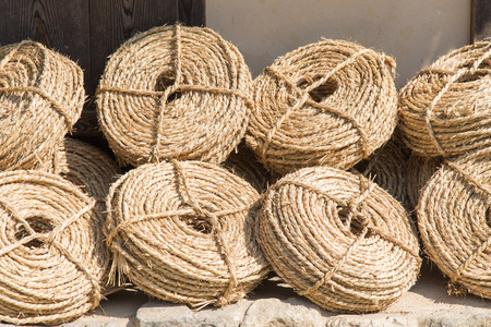 leaned: bunches of straw ropes, leaned against a wall