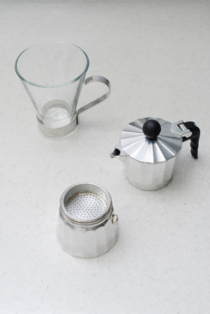 cup and moka pot on a white table photo