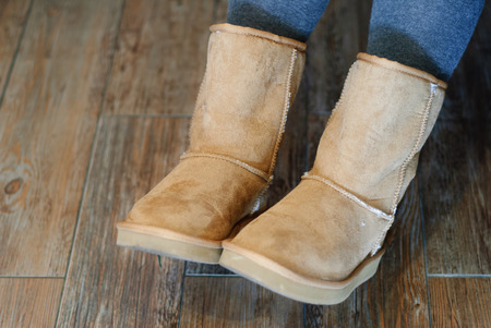 Closeup of brown Ugg boots with wooden background Stockfoto