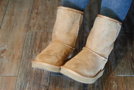 Detalle de botas Ugg marrones con fondo de madera Foto de archivo
