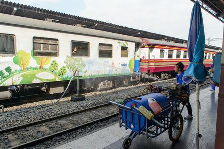 cleaning crew: BANGKOK, THAILAND - DECEMBER 30, 2012: wokers give train a hose in bangkok station.