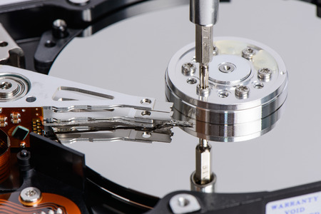 Disassemble Hard disk drive with star shape screw driver. The driver loosen a screw on the platter at the side of head arm. photo