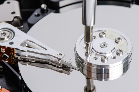 loosen: Disassemble Hard disk drive with star shape screw driver. The driver loosen a screw on the platter at the side of head arm. Stock Photo